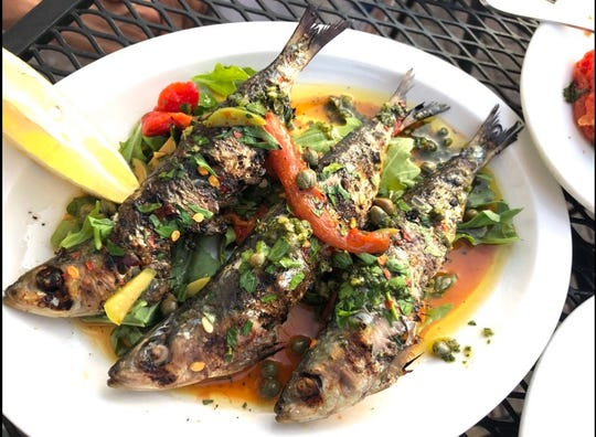 Perfectly grilled sardines, topped with red pepper, capers and olives are a special at Zeppoli in Collingswood.