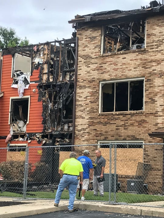 Offiicals inspect the structural stability of a 20-unit condominium building in the Brittany Lakes section of Mount Laurel on Wednesday to determine how much demolition may be necessary after a fire  there Tuesday. All the families have been been displaced  at least temporarily until the building  condition is determined.
