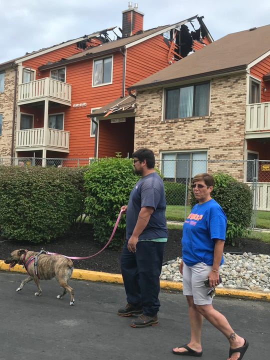 Resident Erick Rodriguez waits with neighbor Lucille Colosimo and his dog, Connie, outside their fire-damaged condominium building Wednesday in Brittany Lakes in Mount Laurel to see if they can return to their homes to retrieve more personal items. Firemen rescued the dog from the Rodriguez condo during the Tuesday fire that displacred 20 families.