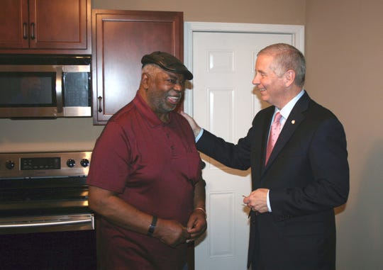 Mayor Joe Pitts presents Marion Watkins Jr. with the keys to his rebuilt home on Cedar Street. HOME,  a federal housing program, provided a low-cost guaranteed loan to Watkins, and the City provided a  25 percent match and managed the project.