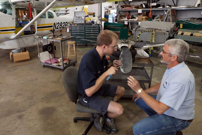 Phil Maddux, right, CEO of MMS Aviation in Coshocton, talks with apprentice mechanic Ryan Hokuf in one of the company's hangers. The company services small aircraft bound for locations around the world for missionary work.