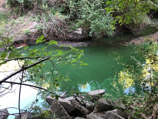 City officials in Clive, Iowa, say an algae bloom caused the water in Walnut Creek to turn bright green.