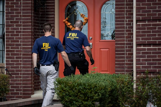 Two FBI agents walk back into UAW President Gary Jones' home in Canton, Wednesday, August 28, 2019.