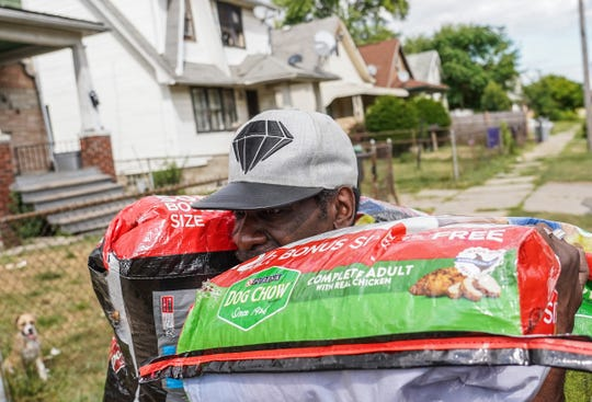 Bobby Fortune of Detroit carries bags of dog food given to him to feed his dogs chained to the fence surrounding his house in Detroit as Detroit Dog Rescue members perform a welfare check while trying to help the owner keep his animals in Detroit on Friday, August 23, 2019.