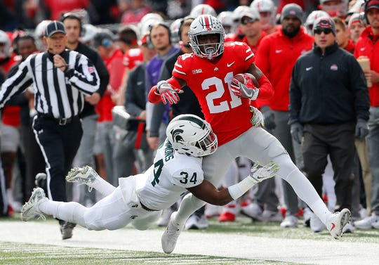 Ohio State Buckeyes wide receiver Parris Campbell (21) is tackled by Michigan State Spartans linebacker Antjuan Simmons (34) during the first quarter at Ohio Stadium.