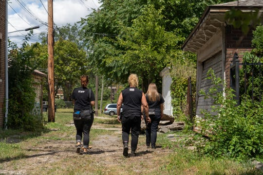 Detroit Dog Rescue workers walk along an alley between houses while doing welfare checks and responding to calls on dogs in the Detroit neighborhood on Friday, August 23, 2019.