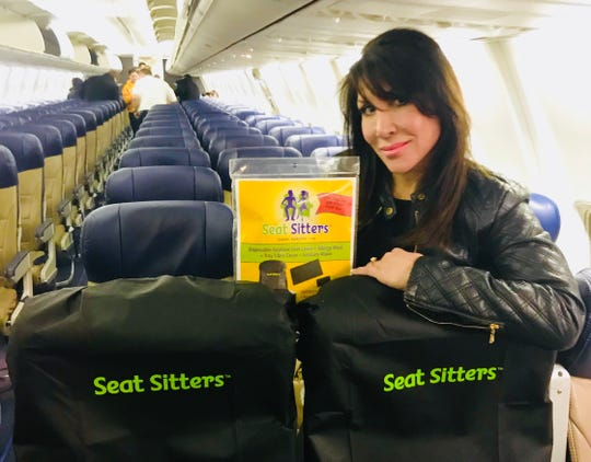 Gina Hoensheid, founder and creator of Seat Sitters, poses with Seat Sitters on an airplane.