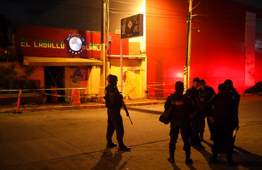 "Police officers guard the scene outside a bar where more than 20 people died in an overnight attack, in Coatzacoalcos, Mexico, early Wednesday, Aug. 28, 2019. President Andres Manuel Lopez Obrador said Wednesday ""the criminals went in, closed the doors, the emergency exits, and set fire to the place."""