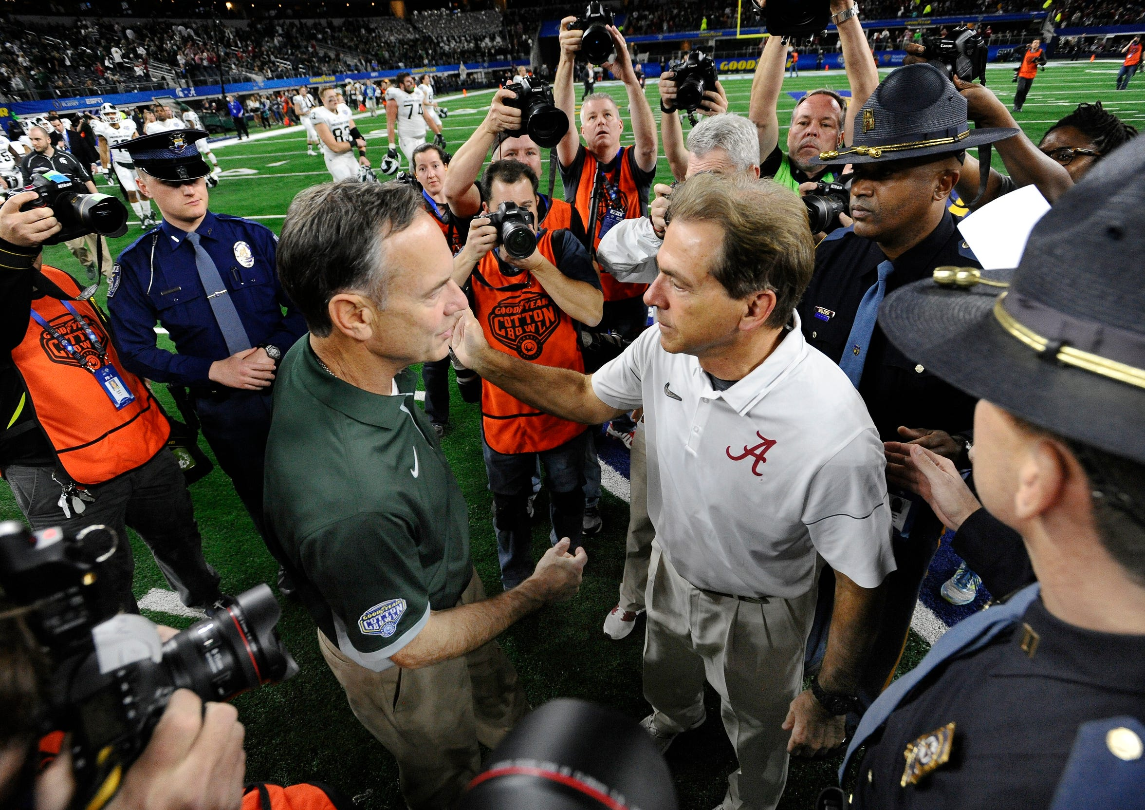 MSU coach Mark Dantonio and Alabama coach Nick Saban meet at the center of the field after the Tide beat the Spartans 38-0.
