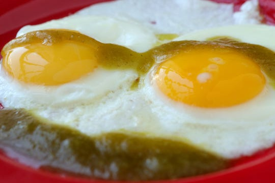 Green hot sauce dresses up sunny side up eggs.