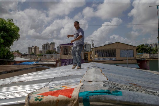 Jorge Ortiz works to tie down his roof as he prepares for the arrival of Tropical Storm Dorian, in the Martín Peña neighborhood of San Juan, Puerto Rico, Tuesday, Aug. 27, 2019. The 50-year-old construction worker was taking no chances as Dorian approached Puerto Rico on Tuesday and threatened to brush past the island's southwest coast at near-hurricane strength.