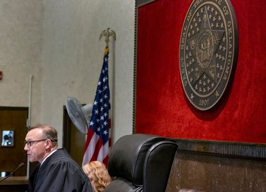 Judge Thad Balkman reads a summary of his decision in the opioid trial at the Cleveland County Courthouse in Norman, Okla., Monday, Aug. 26, 2019. Judge Balkman ruled in favor of the State of Oklahoma, that Johnson and Johnson pay $572 million to a plan to abate the opioid crisis. The proceeding were the first public trial to emerge from roughly 2,000 U.S. lawsuits aimed at holding drug companies accountable for the nation's opioid crisis.