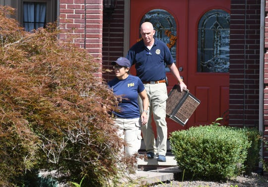 FBI investigators leave the home of UAW President Gary Jones during a search on Wednesday in Canton Township.
