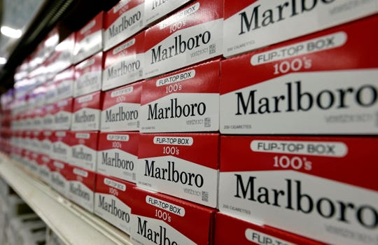 FILE- This June 14, 2018, file photo shows cartons of Marlboro cigarettes on the shelves at JR outlet in Burlington, N.C. Altria confirmed Tuesday, Aug. 27, 2019, that it is in talks to merge with Philip Morris International more than a decade after splitting itself into two companies. Altria has exclusively sold Marlboro and other cigarette brands in the U.S., while Philip Morris has handled international sales.