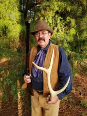 Charles Sacavage is shown dressed as Theodore Roosevelt and is holding a Winchester Model 1894 and elk horn.