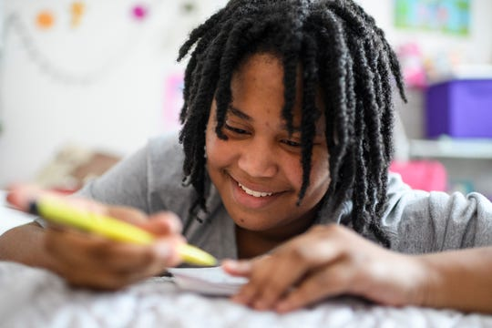 "Deleah Payne, 12, laughs as she accidentally pulls too much lead out of her mechanical pencil while working on an art project on her bed at her home in Evansville, Tuesday evening, Aug. 27, 2019. Her creative flair lead her to write and illustrate a book called ""Our World,"" to educate readers about what it's like for her, and her 6-year-old sister Delynn, to live with autism."