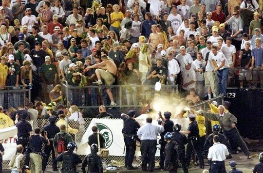 Police, lower right, spray mace into stands after the Colorado State-Colorado football game at Mile High Stadium in Denver on Saturday, Sept. 4, 1999. Fans were throwing bottles at police and members of the Colorado football team as they left the field after the game.