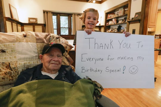 Ed Engle and his great-granddaughter Meah Philbee, 9, hold up a thank-you sign for everyone that sent him a birthday card for his 91st birthday at his home in Kewaunee.