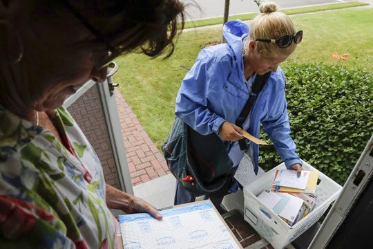 A mail carrier drops off a box of birthday cards and packages for Ed Engle on Aug. 26 at his home in Kewaunee. Hundreds of cards have been pouring in everyday for the 91-year-old Engle, who celebrated his birthday Aug. 23.