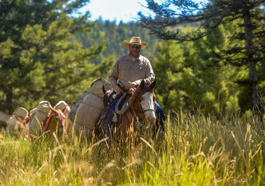 Brady Murphy, a Fish Wildlife Parks game warden in Augusta, rides along the Falls Creek trail during a demonstration for Falls Creek access dedication ceremony in the Helena-Lewis and Clark National Forest, August 27, 2019.