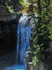 A hiker looks over the edge of a waterfall at Falls Creek Tuesday. Dan Barrett sold 442 acres of land including a stretch along Falls Creek to the Rocky Mountain Elk Foundation, which conveyed it to public ownership via Helena-Lewis and Clark National Forest.