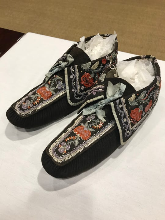 The moccasins have elaborate embroidery that uses moose hair.
