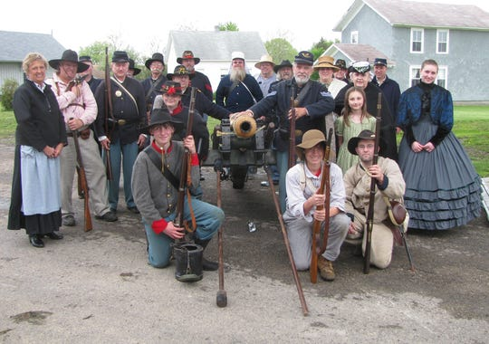 Men, women and children all play roles in the Army of the Southwest reenactments. Their president, O.J. Fargo, is shown at center right with his hand on the cannon. He will speak in North Liberty this Friday.