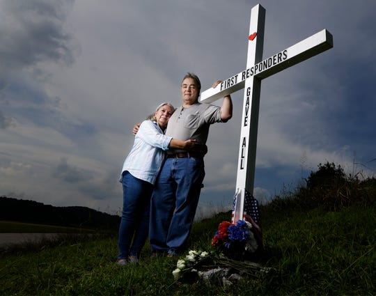 In this Aug. 6, 2019, photo, Ansol and Janie Clark pose at a memorial Ansol Clark constructed near the Kingston Fossil Plant in Kingston, Tenn. The Tennessee Valley Authority was responsible for a massive coal ash spill at the plant in 2008 that covered a community and fouled rivers. The couple says the memorial is for the workers who have come down with illnesses, some fatal, including cancers of the lung, brain, blood and skin and chronic obstructive pulmonary disease. Ansol Clark drove a fuel truck for four years at the cleanup site, and now suffers from a rare blood cancer.