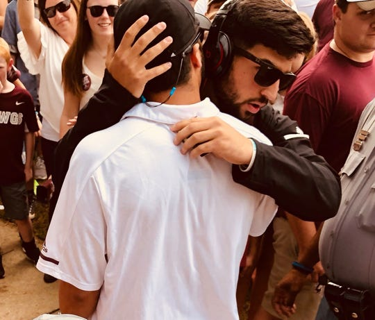 Kyle Schexnayder embraces his brother, Kody, before the latter heads into Davis Wade Stadium for a home football game at Mississippi State.