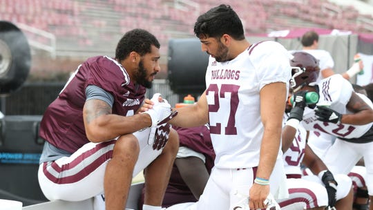 Mississippi State specialist Kody Schexnayder greets former MSU defensive end Montez Sweat during a practice at Davis Wade Stadium.