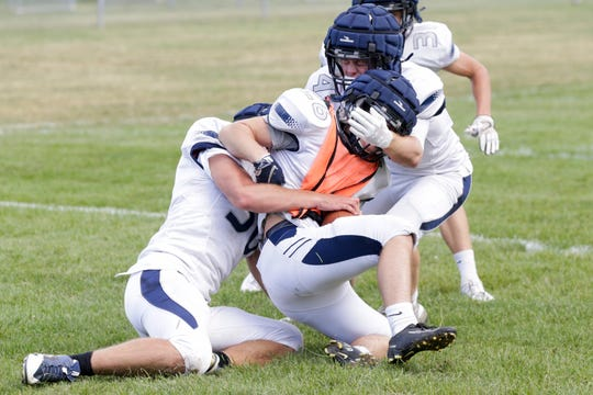 Central Catholic lineman Evan Suppinger (50) and Central Catholic's Daniel Roach (4) tackle a teammate during a football practice, Tuesday, Aug. 27, 2019 in Lafayette.