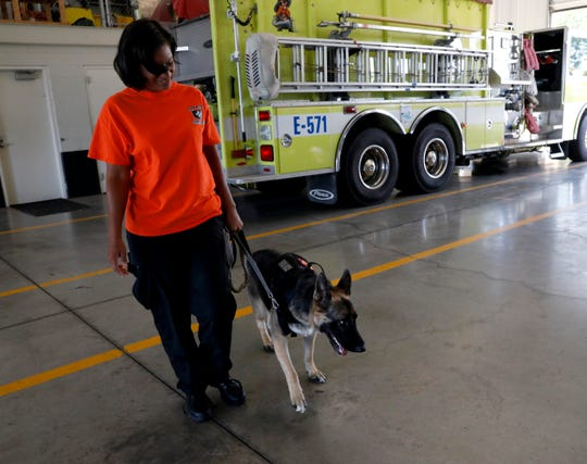 Jeaneene Crowell leads her dog, Sasha, through the truck bays of the Pleasant Township Fire Department Wednesday, Aug. 28, 2019. Sasha is a search and recovery dog and recently became a member of the department.