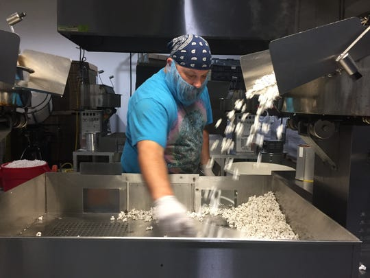 Pop Daddy Popcorn employee Jayson Dillon processes popcorn at the company's Green Oak Township facility, Wednesday, Aug. 28, 2019.