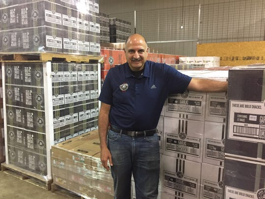 Pop Daddy Popcorn owner Mark Sarafa stands by cases of popcorn and pretzels at his Green Oak Township facility, Wednesday, Aug. 28, 2019.
