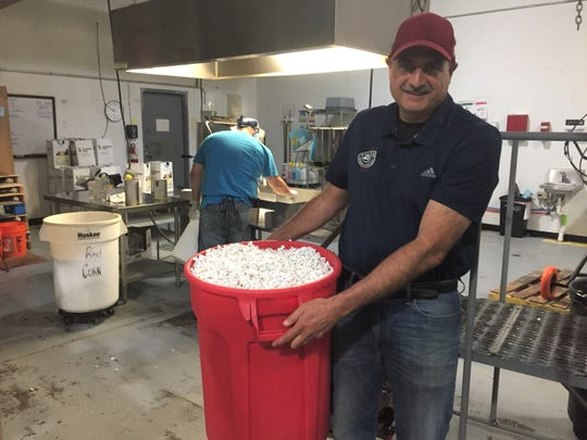 Pop Daddy Popcorn owner Mark Sarafa holds a bucket of just-popped popcorn at his Green Oak Township facility, Wednesday, Aug. 28, 2019.