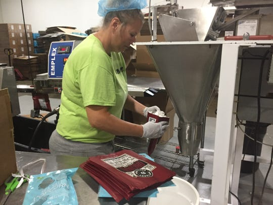 Pop Daddy Popcorn employee Kelly Good bags popcorn at the company's Green Oak Township facility, Wednesday, Aug. 28, 2019.