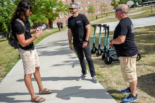 Michigan State University student Alex Blitstein, left, asks Gotcha e-scooters CEO Sean Flood, center, and operations manager Todd Werner questions about the service at a booth on Wednesday, August 28, 2019, on Campus in East Lansing.