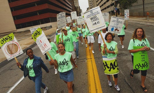 "2002: Members of the Association of Flight Attendants, including Midwest Express attendants, shout ""Chaos"" as they lead the Labor Day March through downtown Milwaukee on Sept. 2, 2002. ""CHAOS"" stands for ""Create Havoc Around Our System."""