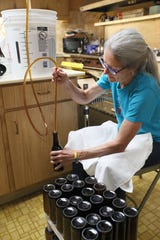 Carol Prchal, part of the Barley Ministries Brewing group at the First Congregational United Church of Christ, fills bottles with the the batch of Oktoberfest they brewed.