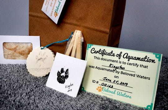 Included in the deluxe aquamation package with Beloved Waters os a fur clipping, an inked paw print, a cement paw print and a certificate of aquamation.