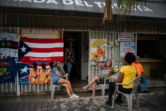 People drink beer on a patio before the arrival of Tropical Storm Dorian in Boqueron, Puerto Rico, Tuesday, Aug. 27, 2019.
