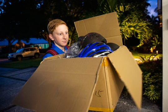 Cooper Tunkle, an eighth-grader at Gulfview Middle School, packages donated helmets at home on Wednesday, Aug. 28, 2019, in Naples.