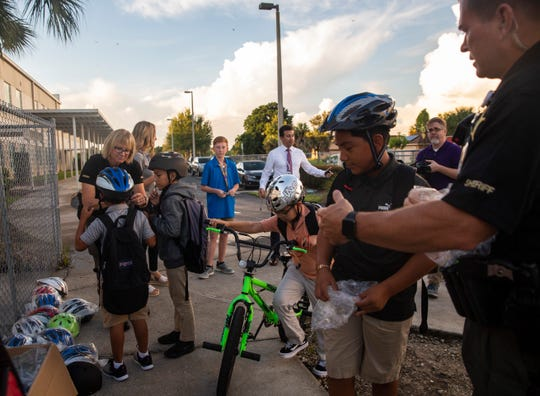 "Students from Golden Gate Elementary School try on helmets on Wednesday, Aug. 28, 2019. Cooper Tunkle, an eighth-grader at Gulfview Middle School, started a charity called ""Cooper's Helmet Hero"" to help provide bike helmets."