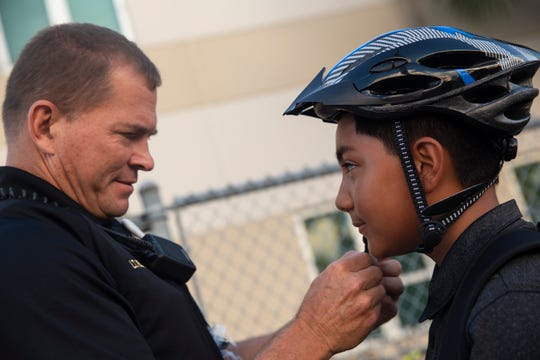 Collier Sheriff deputy Jeffrey Boyd puts bike helmet on Arturo Hernandez Almaraz at Golden Gate Elementary School on Wednesday, Aug. 28, 2019.