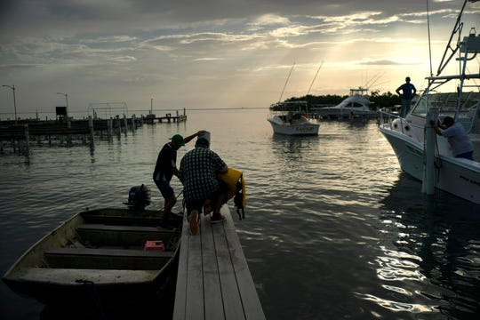 People arrive to a private harbor to move boats away for protection ahead of the arrival of Tropical Storm Dorian in Boqueron, Puerto Rico, Tuesday, Aug. 27, 2019.