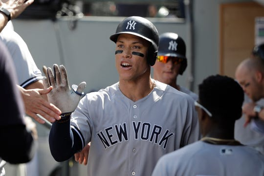 New York Yankees' Aaron Judge is greeted in the dugout after he hit a two-run home run during the fifth inning of a baseball game against the Seattle Mariners, Wednesday, Aug. 28, 2019, in Seattle. (AP Photo/Ted S. Warren)