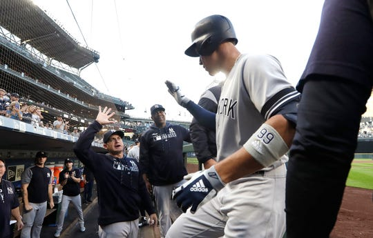 New York Yankees' Aaron Judge is congratulated by teammates as he enters the dugout after his two-run home run against the Seattle Mariners during the first inning of a baseball game Tuesday, Aug. 27, 2019, in Seattle. (AP Photo/Elaine Thompson)