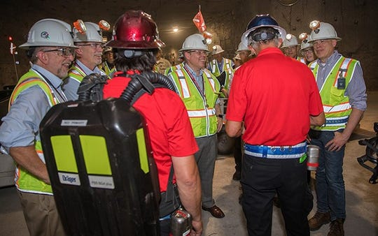 Ike White, center, Senior Advisor for EM, receives a briefing from members of the Waste Isolation Pilot Plant (WIPP) award-winning mine rescue teams as part of an underground tour at the WIPP site. Also on the tour, at far right, is New Mexico Environment Department Secretary James C. Kenney.