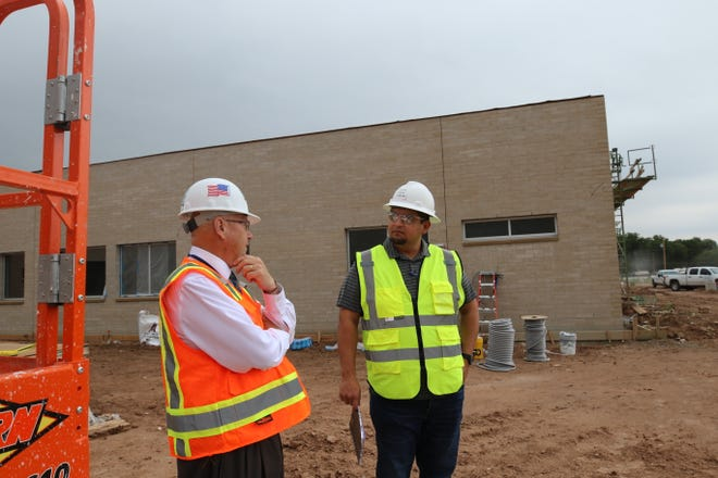 Dr. Gerry Washburn, left, Superintedent of Carlsbad Schools, and Juan Dorado, right, of Dekker/Perich/Sabatini on Aug. 29 outside of Cottonwood Elementary School. The school is currently under construction and is expected to be opened to students in January 2020.