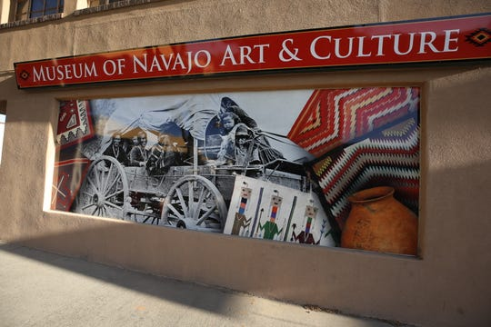 A colorful, eye-catching graphic display in one of the windows at the Museum of Navajo Art and Culture is topped by a lighted sign.